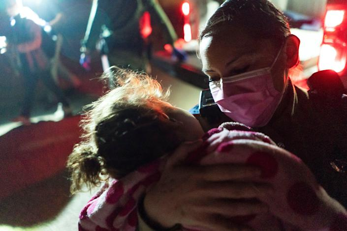 <p>A Texas Highway Patrol officer tries to comfort an asylum-seeking migrant girl as she waits to be transported by the US Border Patrols after crossing the Rio Grande river into the US from Mexico</p> (Reuters)