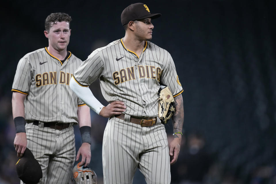 San Diego Padres third baseman Manny Machado, front, and second baseman Jake Cronenworth wait for relief pitcher Nabil Crismatt to take the mound in the eighth inning of the team's baseball game against the Colorado Rockies on Tuesday, June 15, 2021, in Denver. (AP Photo/David Zalubowski)