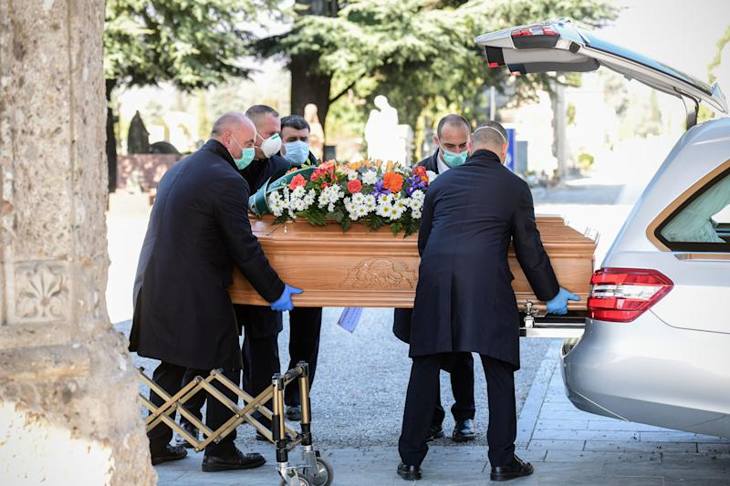 Undertakers wearing a face mask carry a coffin out of a hearse on March 16, 2020 at the Monumental cemetery of Bergamo, Lombardy, as burials of people who died of the new coronavirus are being conducted at the rythm of one every half hour. (Photo by Piero Cruciatti / AFP) (Photo by PIERO CRUCIATTI/AFP via Getty Images)