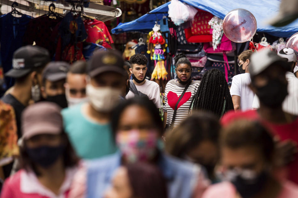 FILE - In this Dec. 23, 2020 file photo, pedestrians shop in an outdoor market area, days before a COVID-19 lockdown goes into effect in Sao Paulo, Brazil. Brazil has suffered more than 200,000 COVID-19 deaths, the second-highest total in the world after the United States, with infections and deaths surging again. (AP Photo/Carla Carniel)