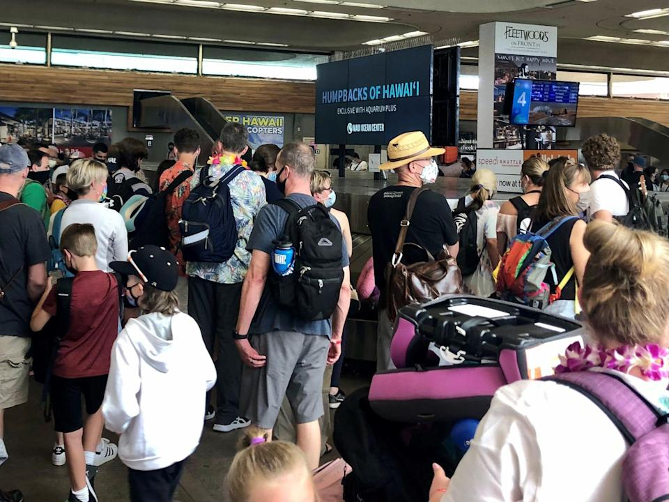 Travelers arriving at Maui's Kahului Airport wait for their bags on June 29. The airport is packed as tourists return in droves. Masks are required.