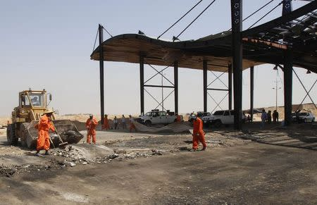 Municipality workers clean up at the site of a bomb attack at a checkpoint in the city of Kirkuk July 12, 2014. REUTERS/Ako Rasheed