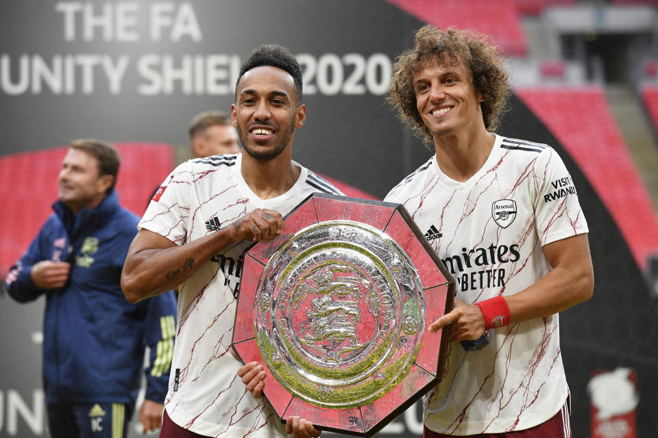 Arsenal's Pierre-Emerick Aubameyang and David Luiz, right, pose with the trophy at the end of the English FA Community Shield soccer match between Arsenal and Liverpool at Wembley stadium in London, Saturday, Aug. 29, 2020. Arsenal defeated Liverpool 5-4 in a penalty shootout after the game ended tied 1-1. (Justin Tallis/Pool via AP)