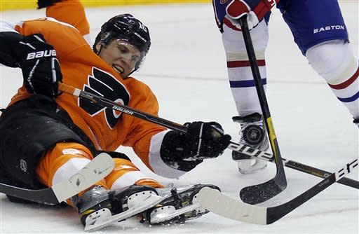 Philadelphia Flyers center Brayden Schenn (10) works the puck even while lying on the ice in the second period of an NHL hockey game with the Montreal Canadiens, Saturday, March 24, 2012, in Philadelphia. (AP Photo/Alex Brandon)