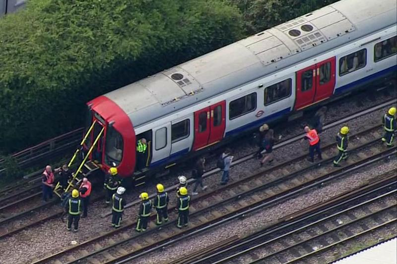 Emergency workers help people to disembark a train near the Parsons Green Tube bombing (Pool via AP)