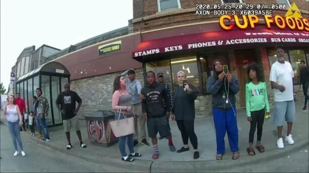 This image from a police body camera shows people gathering as Chauvin presses his knee on Floyd's neck outside the Cup Foods convenience store in Minneapolis on May 25, 2020. Floyd later died in hospital. (Minneapolis Police Department/The Associated Press - image credit)