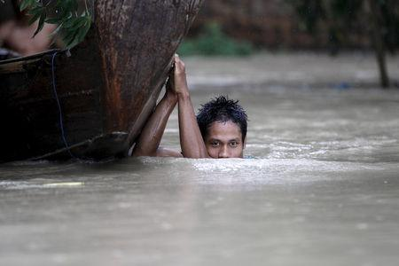 A boy moves his boat in a flooded village outside Zalun Township, Irrawaddy Delta, Myanmar, August 6, 2015.  REUTERS/Soe Zeya Tun