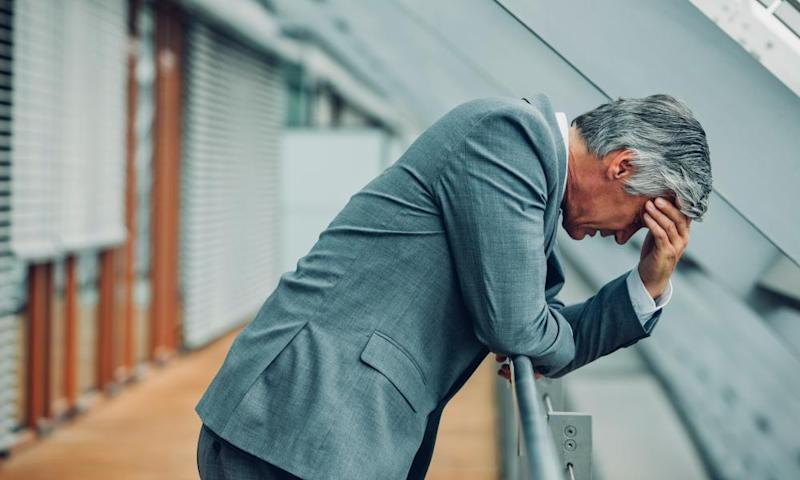 Desperate businessman leaning on railing