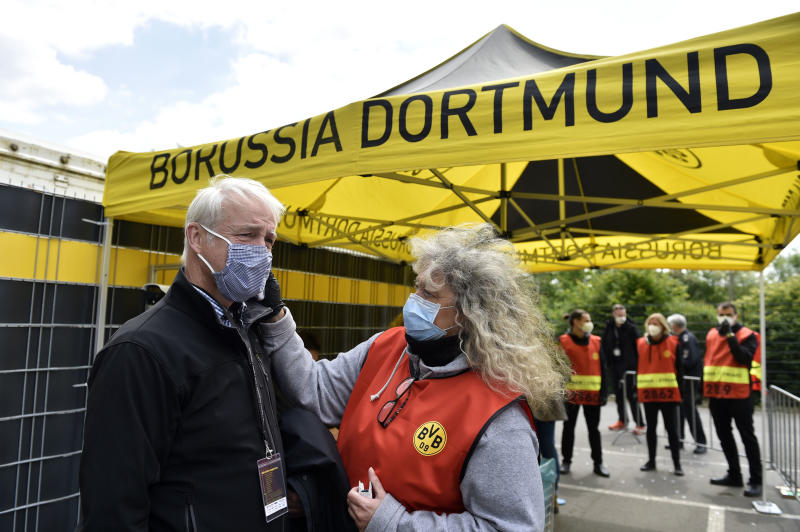 A TV crew member has his temperature checked before entering the stadium for the German Bundesliga soccer match between Borussia Dortmund and Schalke 04 in Dortmund, Germany. (Photo by Martin Meissner/PA Images via Getty Images)