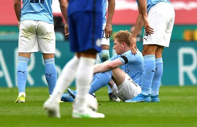Kevin De Bruyne sits on the pitch injured