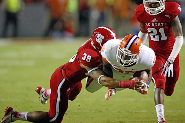 Clemson's D.J. Howard, center, dives for extra yards in the grasp of North Carolina State's Brandon Pittman (39) with NC State's Niles Clark (21) nearby during the second half of an NCAA college football game in Raleigh, N.C., Thursday, Sept. 19, 2013. Clemson won 26-14. (AP Photo/Karl B DeBlaker)