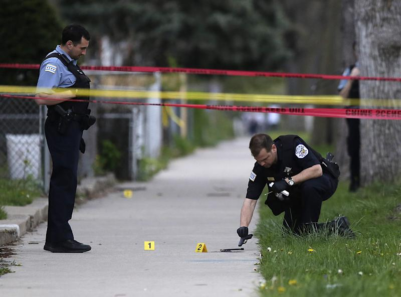 A Chicago Police officer, left, watches as an evidence technician officer investigates a gun at the scene where a 16-year-old boy was shot in the head and killed and another 18-year-old man was shot and wounded on the 7300 block of South Sangamon Street on April 25, 2016 in Chicago, Illinois. (Photo: Joshua Lott/Getty Images)