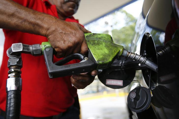 A man pumps gasoline at a service station in Caracas