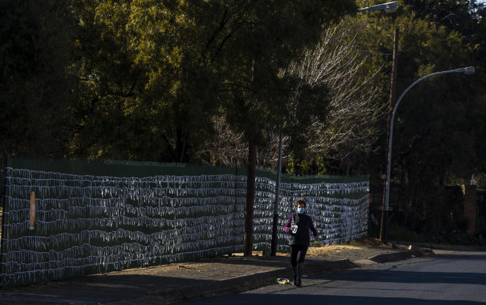 """FILE - In this July 29, 2020, file photo, a woman wearing a face mask to protect against the spread of the coronavirus, walks past ribbons tired onto the fence to represent South Africans who have died from COVID-19, at St James Presbyterian church in Bedford Gardens, Johannesburg, South Africa. Africa's confirmed coronavirus cases have surpassed 1 million, but global health experts tell The Associated Press the true toll is several times higher. Whatever Africa's real coronavirus toll, the church has quietly been marking the country's """"known"""" number of deaths by tying white ribbons to its fence. The project's founders say each ribbon really stands for multiple people. (AP Photo/Themba Hadebe, File)"""