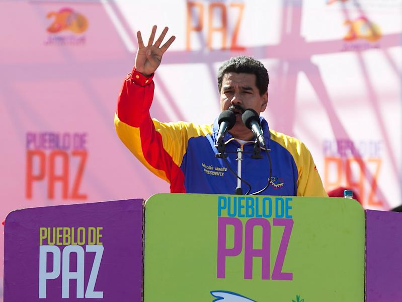 """Venezuela's President Nicolas Maduro speaks during a rally on Bolivar Avenue in downtown Caracas, Venezuela, Saturday, Feb. 15, 2014. The signs read in Spanish """"People of peace."""" Maduro said a police manhunt is underway for opposition leader Leopoldo Lopez, and denounced what he said is a """"fascist"""" plot to oust him from power. (AP Photo/Alejandro Cegarra)"""