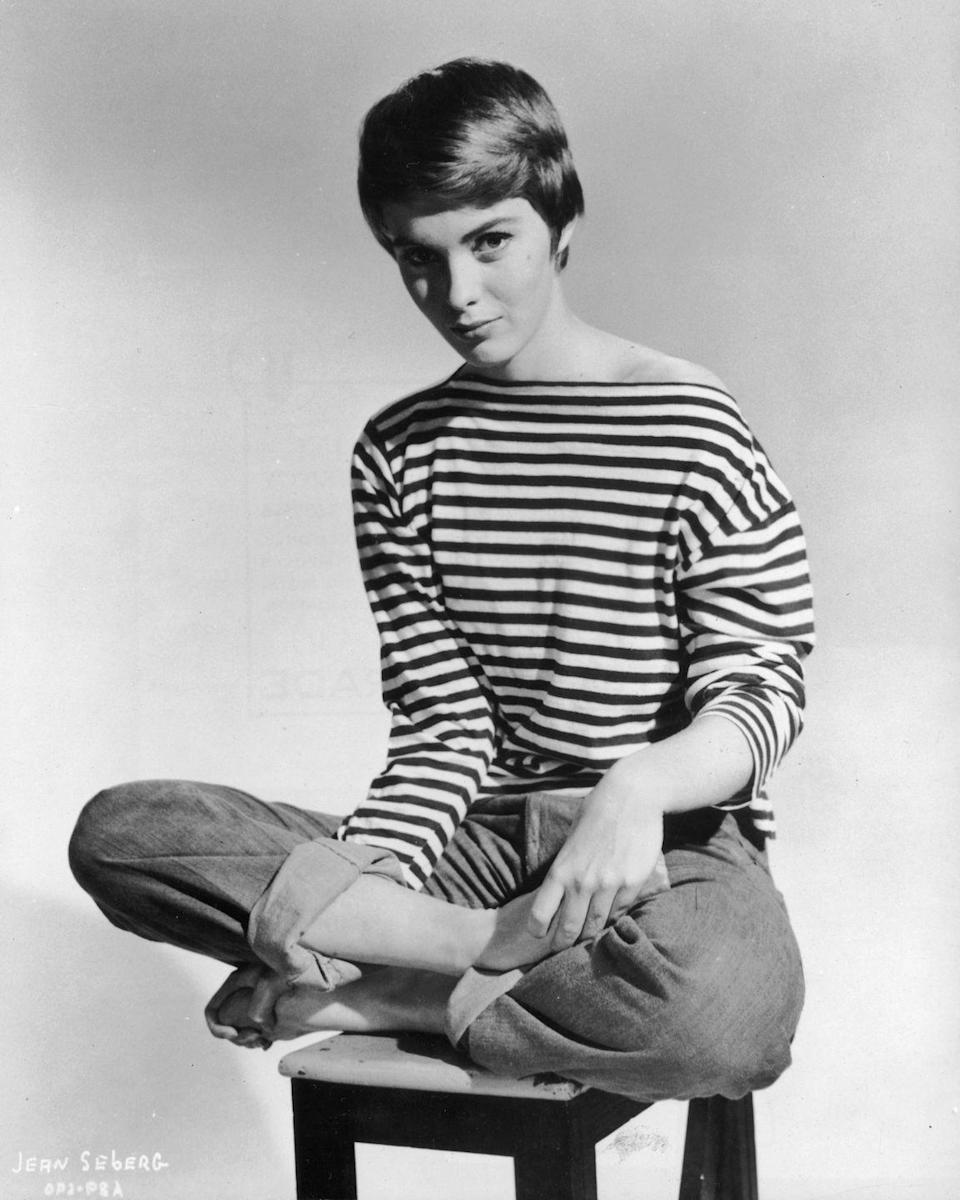 <p>Jean Seberg rolls her blue jeans and pairs with another iconic complement: the striped tee. (Seberg, an American originally, moved to France for a few years, and when asked by a Toledo newspaper what she missed most about the U.S., blue jeans were high on her list.)</p>