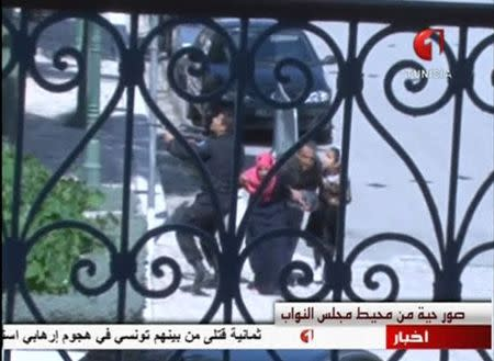 A still image taken from video shows tourists running for cover as an armed man stands guard at Tunisia's national museum in Tunis March 18, 2015. REUTERS/Tunisia TV handout via Reuters TV