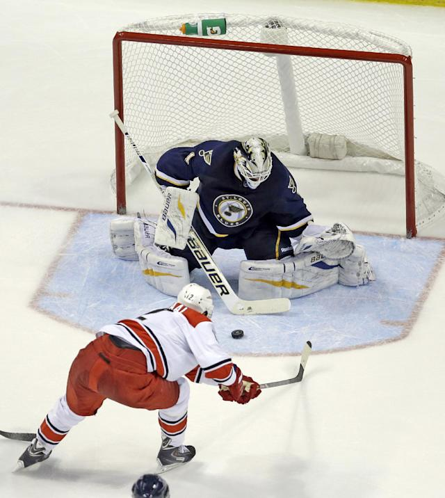 Carolina Hurricanes' Eric Staal, bottom, slips a puck past St. Louis Blues goalie Brian Elliott to score during the second period of an NHL hockey game Saturday, Nov. 16, 2013, in St. Louis. (AP Photo/Jeff Roberson)