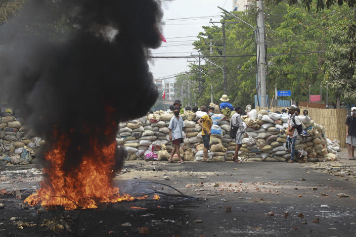 FILE - In this March 30, 2021, file photo, anti-coup protesters stand beside burning tires as they fortify their position against the military during a demonstration in Yangon, Myanmar. One hundred days since their takeover, Myanmar's ruling generals maintain just the pretense of control over the country. There are fears the military takeover is turning Myanmar into a failed state. (AP Photo, File)