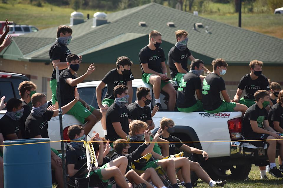Smithville football players watched from the sidelines as parade-goers drove past to cheer them on. (Photo: Angelica Matthews)
