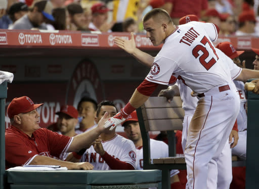 Los Angeles Angels' Mike Trout is greeted in the dugout after scoring on a hit by Howie Kendrick during the first inning of a baseball game against the Miami Marlins in Anaheim, Calif., Tuesday, Aug. 26, 2014. (AP Photo/Chris Carlson)
