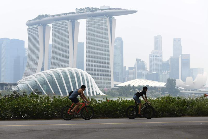 People cycle before the city skyline on a hazy day in Singapore on September 15, 2019. - Pollution from forest fires in Indonesia pushed Singapore's air quality to unhealthy levels for the first time in three years on September 14, the government said, a week ahead of the Formula One night race in the city. (Photo by ROSLAN RAHMAN / AFP) (Photo credit should read ROSLAN RAHMAN/AFP via Getty Images)