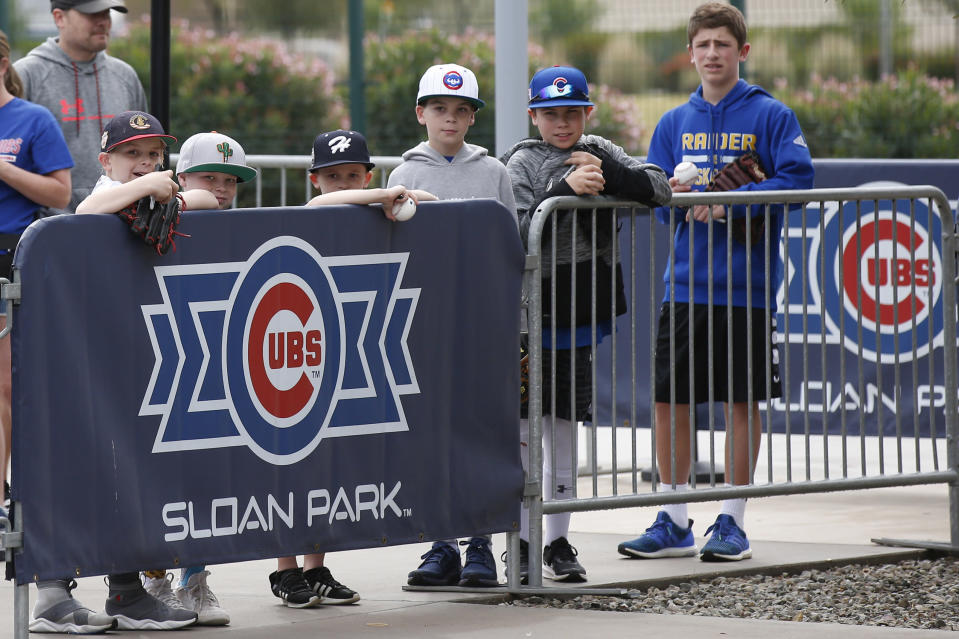 FILE - Young fans look out to the practice fields after a spring training baseball game between the Los Angeles Dodgers and the Chicago Cubs was canceled for inclement weather, at Sloan Park in Mesa, Ariz., in this Thursday, March 12, 2020, file photo. Big league managers say that Major League Baseball has instructed them to prepare for spring training to start on time in mid-February despite uncertainty around the coronavirus. Tampa Bay Rays manager Kevin Cash said Wednesday, Dec. 16, 2020, that officials from the commissioner's office had a meeting with managers Tuesday an expressed optimism about opening spring camps as scheduled. (AP Photo/Sue Ogrocki, File)