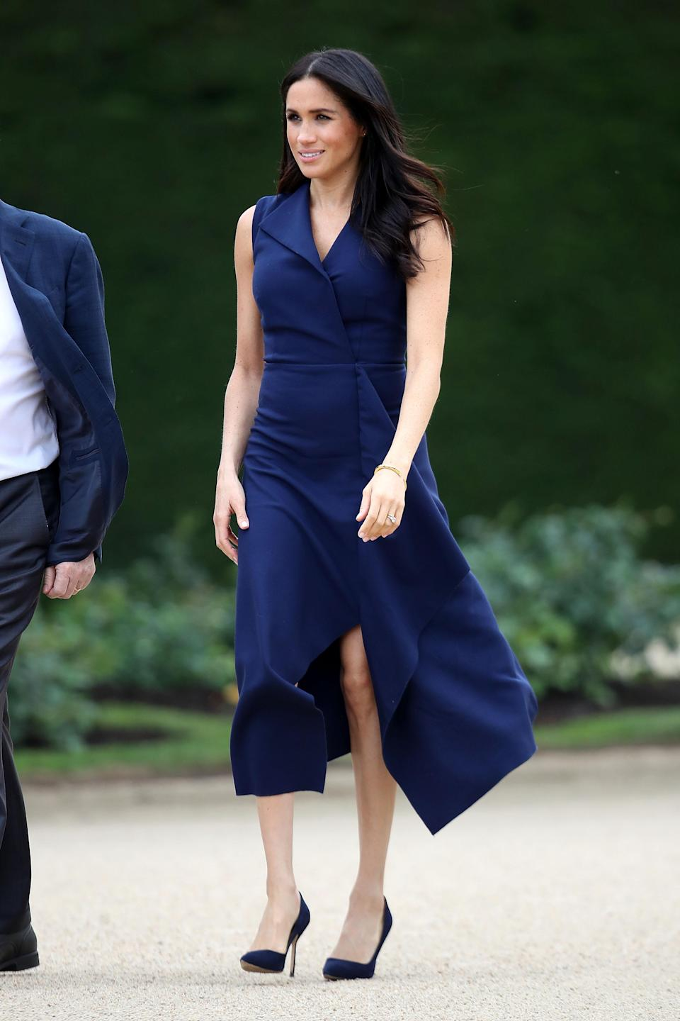 <p>Meghan wore a custom-made navy blue dress by Australian designer Dion Lee for a reception at Government House Victoria. She accessorised with a pair of Manolo Blahnik 'BB' shoes and a Shaun Leanne 'Tusk' diamond bracelet. <em>[Photo: Getty]</em> </p>