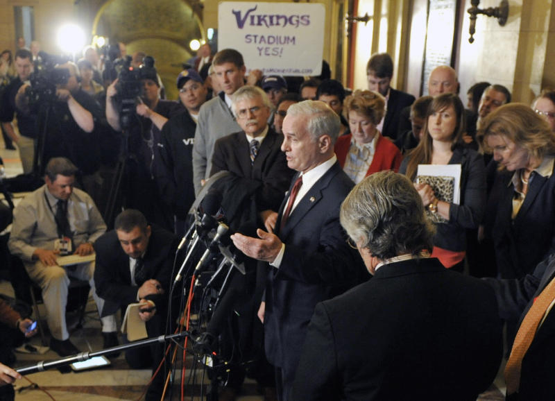 Minnesota Gov. Mark Dayton, center, addresses the media at the State Capitol Friday, April 20, 2012, in St. Paul, Minn., after he, NFL commissioner Roger Goodell and legislative leaders met in an effort to get a bill passed for a new Minnesota Vikings NFL football stadium. (AP Photo/Jim Mone)