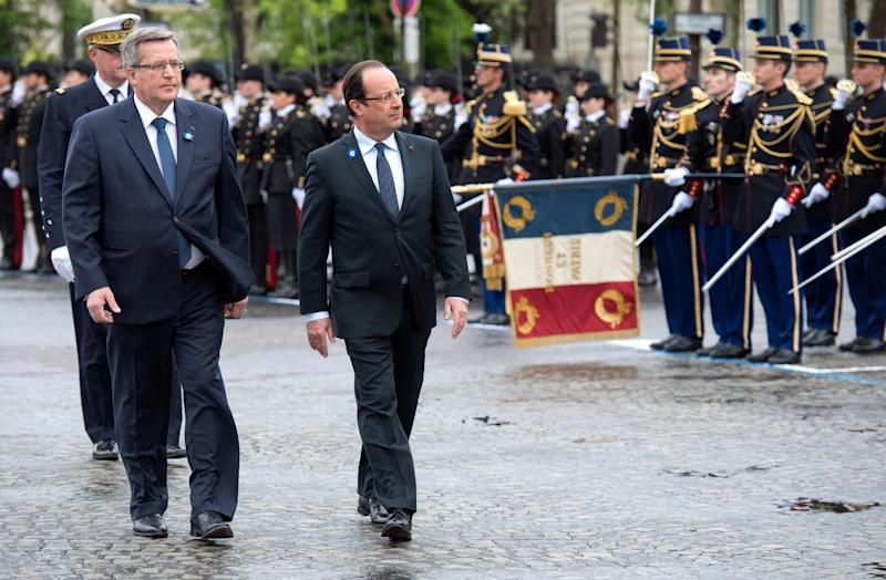Polish President Bronislaw Komorowski, left, and French President Francois Hollande, right, review the troops during a ceremony marking the 68th anniversary of the end of World War II in Europe, in Paris, Wednesday, May 8, 2013. (AP Photo/Bertrand Langlois, Pool)