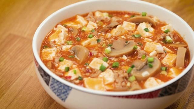 mapo tofu with canned mushrooms garnished with spring onions in a white bowl