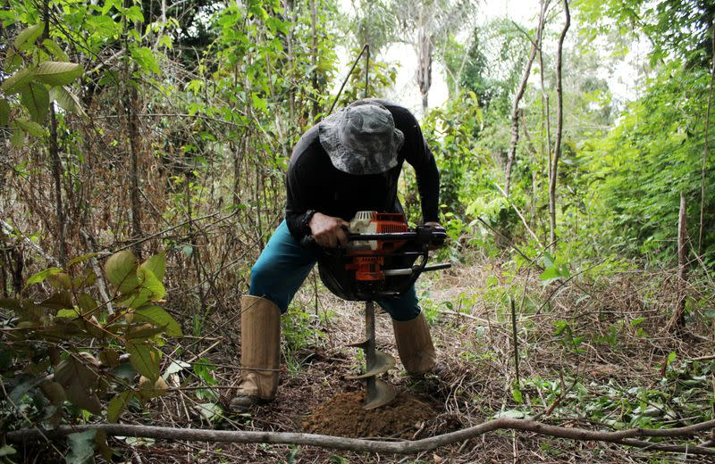 Day laborer Ivan Batista Queiroz helps take soil samples while measuring carbon content on a parcel of Amazon rainforest in Itapua do Oeste