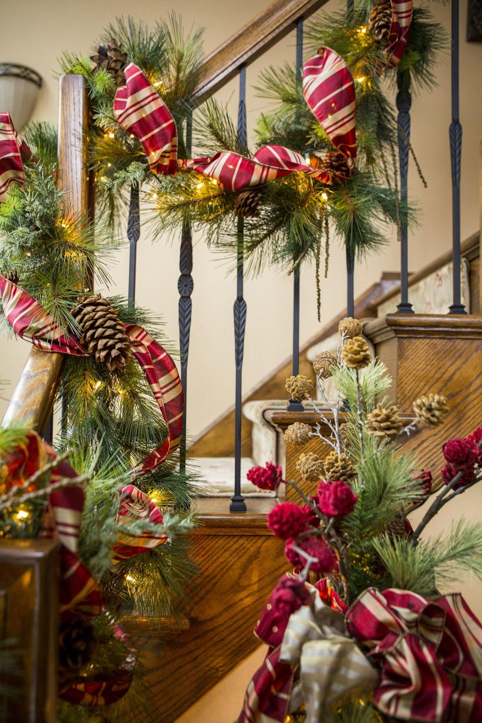 """<p>When it comes to <a href=""""https://www.thepioneerwoman.com/home-lifestyle/crafts-diy/g33549660/christmas-decoration-ideas/"""" rel=""""nofollow noopener"""" target=""""_blank"""" data-ylk=""""slk:Christmas decorations"""" class=""""link rapid-noclick-resp"""">Christmas decorations</a>, a <a href=""""https://www.thepioneerwoman.com/holidays-celebrations/a37668896/how-to-keep-christmas-tree-alive/"""" rel=""""nofollow noopener"""" target=""""_blank"""" data-ylk=""""slk:Christmas tree"""" class=""""link rapid-noclick-resp"""">Christmas tree </a>is always the center of attention. But if you have a stairway in your home—whether it's in the foyer or another part of the house—the holidays are its moment to shine! Christmas stair decorations can be as simple or as ornate as you like. <a href=""""https://www.thepioneerwoman.com/holidays-celebrations/g37575829/christmas-garland-ideas/"""" rel=""""nofollow noopener"""" target=""""_blank"""" data-ylk=""""slk:Christmas garland"""" class=""""link rapid-noclick-resp"""">Christmas garland</a> made with live greens look beautiful and smell just as lovely. Pretty lights also make a great addition to Christmas decor for stair railings, and there are so many affordable options with battery-operated strings on timers—so you don't have to worry about finding an outlet or tripping on cords. </p><p>If that seems like too much work, arrange a few small <a href=""""https://www.thepioneerwoman.com/home-lifestyle/gardening/g37711385/christmas-plants/"""" rel=""""nofollow noopener"""" target=""""_blank"""" data-ylk=""""slk:Christmas plants"""" class=""""link rapid-noclick-resp"""">Christmas plants</a> (such as <a href=""""https://www.thepioneerwoman.com/home-lifestyle/gardening/a37694453/poinsettia-care/"""" rel=""""nofollow noopener"""" target=""""_blank"""" data-ylk=""""slk:poinsettias"""" class=""""link rapid-noclick-resp"""">poinsettias</a>!) and decorative lanterns at the bottom of your stairs, or place LED candles on every other step. This is a super simple way to make the stairs look special without a lot of fussing. Another fun idea is taking your collection of <a href=""""https://"""