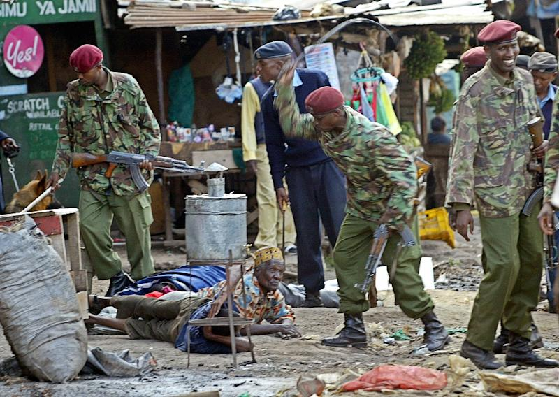 An armed police officer whipping suspects who were rounded-up during a police crackdown on the banned Mungiki sect in Nairobi's Mathare slum in 2007 (AFP Photo/Tony Karumba)