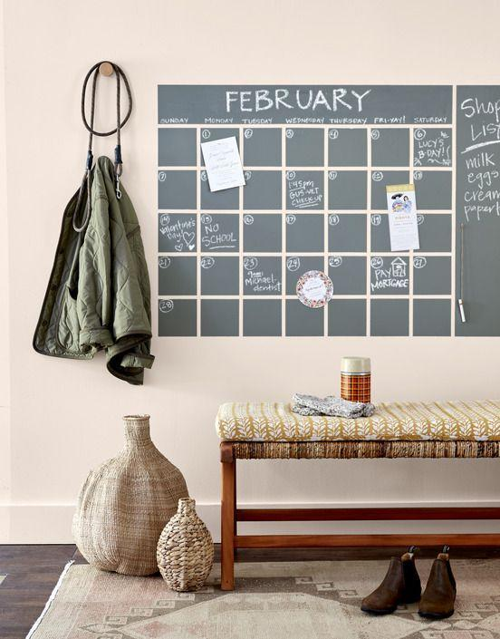 <p>Keep everyone in the loop with an entryway wall calendar. Use painter's tape (we used a 1/2-inch-wide roll) to tape off a 35-square grid to desired size, as well as two rectangles, as shown. Paint with acrylic chalkboard paint (we used Behr's Interior Chalk Decorative Paint). Once dry, remove tape, and touch up any rough edges. Tie a length of twine around a piece of chalk, knot end, and hang on wall with a pushpin. </p>