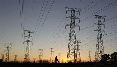 A man walks past electricity pylons as he returns from work in Soweto, outside Johannesburg