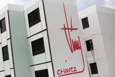 A woman stands at a window of a building bearing a design of the signature of late Venezuelan President Hugo Chavez in Ciudad Caribia outside Caracas in this September 19, 2013 file photo. REUTERS/Jorge Silva/Files
