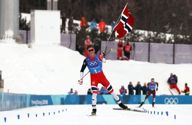 Cross-Country Skiing - Pyeongchang 2018 Winter Olympics - Men's 4x10 km Relay - Alpensia Cross-Country Skiing Centre - Pyeongchang, South Korea - February 18, 2018 - Johannes Hoesflot Klaebo of Norway holds up his national flag. REUTERS/Jorge Silva