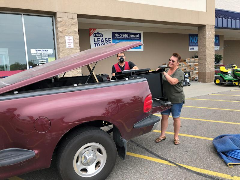 Stephanie McRae uses her husband's 1997 Ford F-150 to pick up a pellet smoker from Lowe's in Fort Gratiot on Sunday for Father's Day. She said her husband would give up cable TV to keep his truck, but not coffee, no way.
