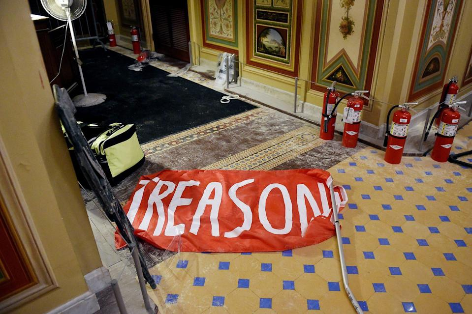 <p>A flag reading 'treason' was left behind on the floor of the U.S. Capitol building, along with other debris.</p>
