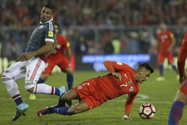 "Chile's <a class=""link rapid-noclick-resp"" href=""/soccer/players/alexis-sánchez"" data-ylk=""slk:Alexis Sanchez"">Alexis Sanchez</a>, right, falls as he fights for the ball with Paraguay's Richard Ortiz, left, during a 2018 World Cup qualifying soccer match in Santiago, Chile, Thursday, Aug. 31, 2017. (AP Photo/Esteban Felix)"