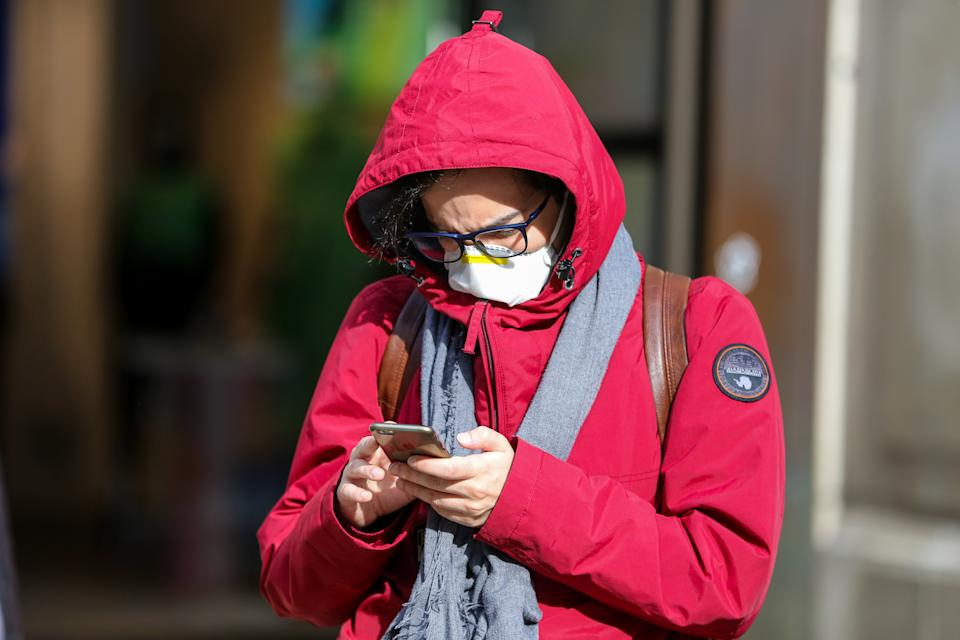 A man wearing a face mask as a preventive measure against the corona virus views his mobile phone in central London. 8 people have died from the virus and the number of coronavirus cases in the UK has increase to 456. (Photo by Steve Taylor / SOPA Images/Sipa USA)