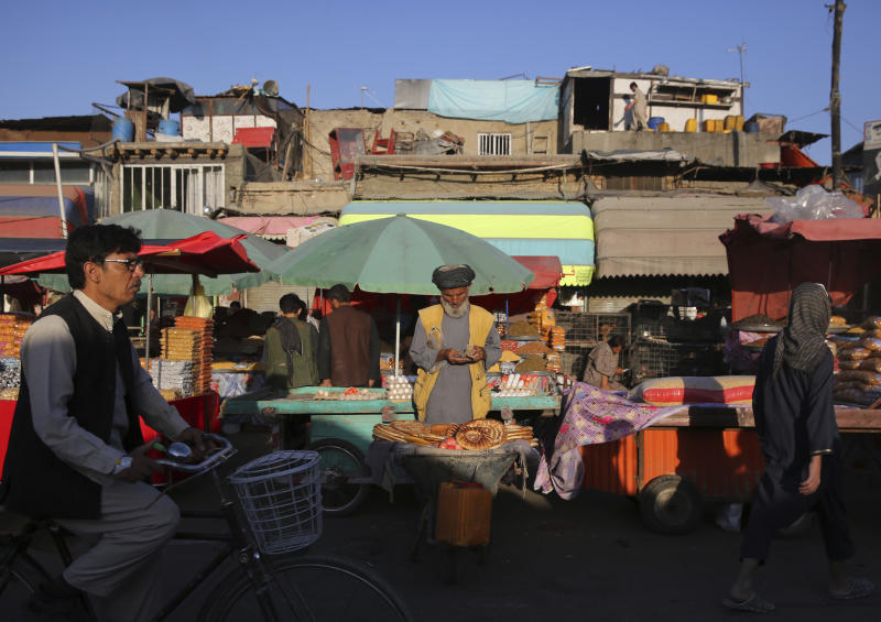 A roadside bread seller counts money as he waits for customers at a market in Kabul, Afghanistan, Tuesday, Aug. 6, 2019. (AP Photo/Rafiq Maqbool)