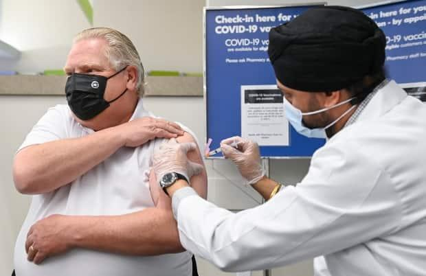 Ontario Premier Doug Ford receives the AstraZeneca vaccine against COVID-19 from pharmacist Anmol Soor at a Toronto drug store on Friday, April 9.