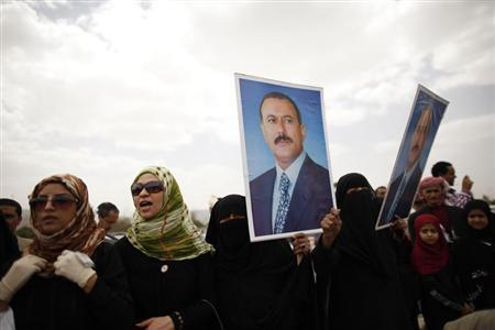 Supporters of Yemen's former President Ali Abdullah Saleh hold posters of Saleh outside the al-Saleh mosque after weekly Friday prayers in Sanaa