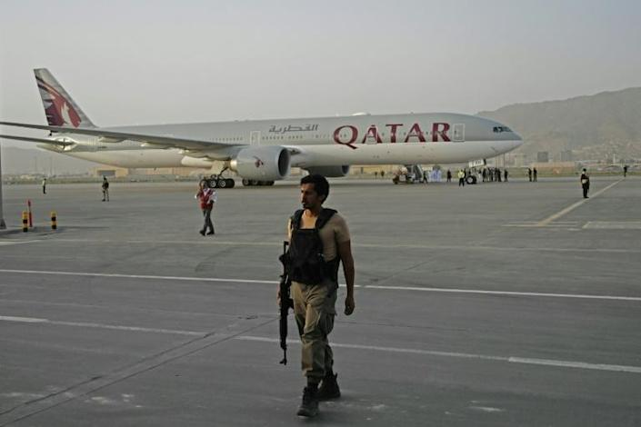 A Qatari security officer stood guard as evacuees boarded the Qatar Airways aircraft bound for Doha at the airport in the Afghan capital Kabul on September 10, 2021 (AFP/Aamir QURESHI)