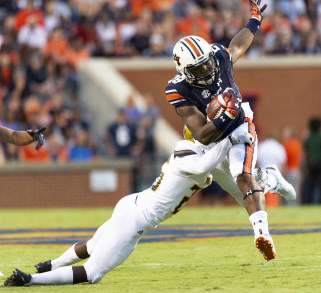 Auburn running back JaTarvious Whitlow (28) tries to get past Alabama State defensive back Kimar Martin (26) during the first half of an NCAA college football game Saturday, Sept. 8, 2018, in Auburn, Ala. (AP Photo/Vasha Hunt)