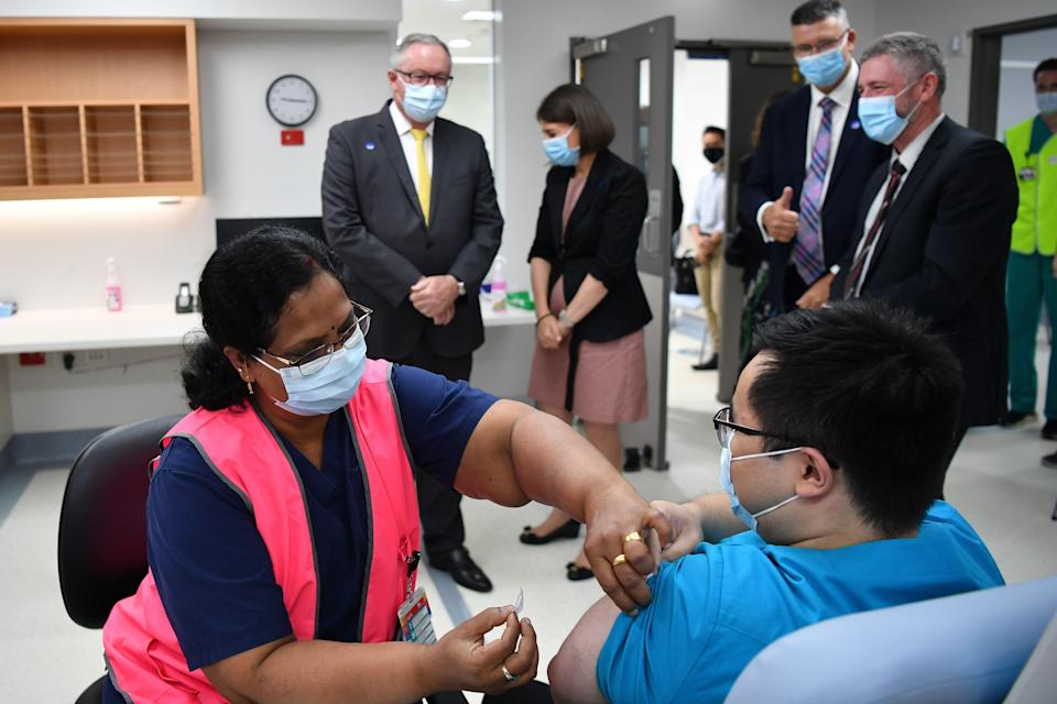 NSW Health Minister Brad Hazzard, left, and Premier Gladys Berejiklian look on Monday as NSW Health worker Andrew Santoso, a radiographer, receives his COVID-19 vaccination at Westmead Hospital. (Photo: Dean Lewins - Pool/Getty Images)