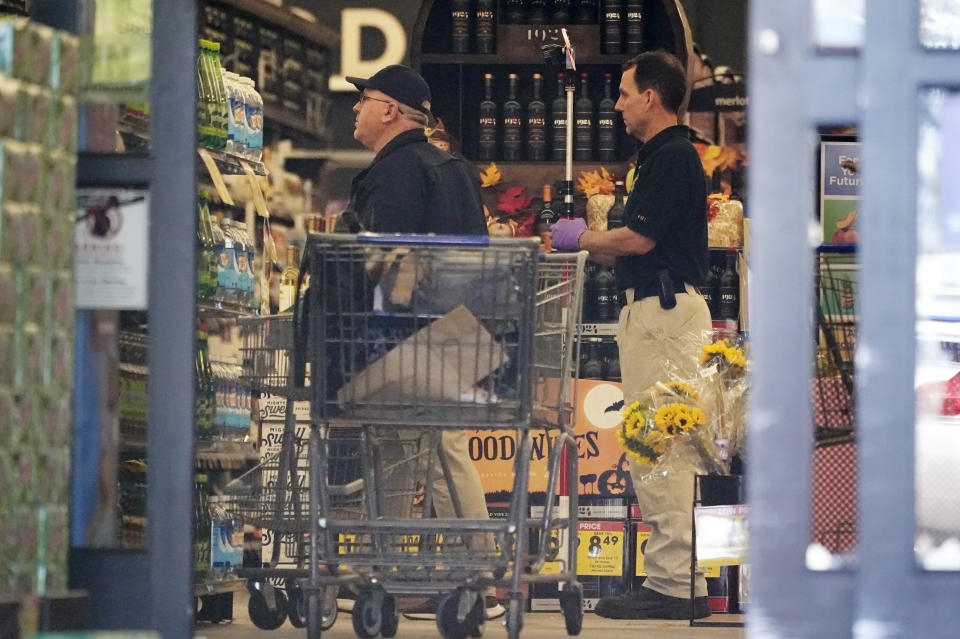Investigators work inside a Kroger grocery store Friday, Sept. 24, 2021, in Collierville, Tenn. Police say a gunman, who has been identified as a third-party vendor to the store, attacked people Thursday and killed at least one person and wounded others before being found dead of an apparent self-inflicted gunshot wound. (AP Photo/Mark Humphrey)