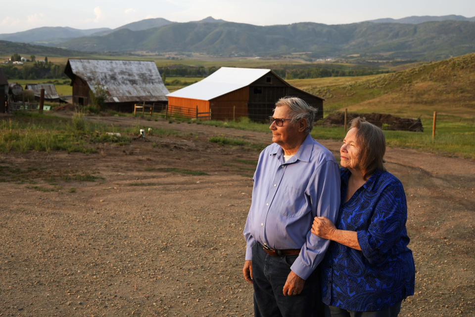 Third-generation cattle ranchers Jim Stanko, left, and his wife, Jo Stanko, pose for a photo as they stand together on their land near Steamboat Springs, Colo., Wednesday, July 14, 2021. Jim says due to drought conditions this year, he may have to sell some of their herd if he can't harvest enough hay to feed them. (AP Photo/Brittany Peterson)